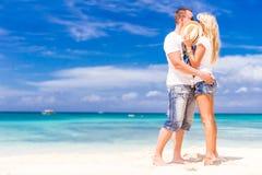 Junge liebevolle Paare, die auf tropischem Strand des Sandes auf blauem Himmel sich entspannen Stockfoto