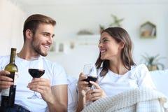 Junge liebevolle Paare, die ein Glas Rotwein in ihrem Wohnzimmer trinken lizenzfreie stockbilder