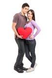 Junge liebevolle Paare, die ein Kissen anhalten Lizenzfreies Stockfoto