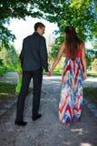 Junge liebevolle Paare, die Hände in einem Sommerpark anhalten Lizenzfreies Stockbild