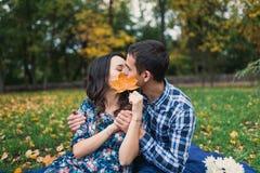 Junge liebevolle Paare, die hinter großem Blatt, versteckter Kuss küssen Stockbild