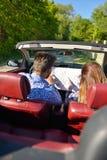 Junge liebevolle Paare, die ihr romantisches Abenteuer planen Frohe junge lächelnde Paare beim Reiten in ihr Kabriolett Lizenzfreies Stockfoto