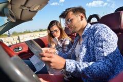 Junge liebevolle Paare, die ihr romantisches Abenteuer planen Frohe junge lächelnde Paare beim Reiten in ihr Kabriolett Lizenzfreie Stockfotos