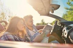 Junge liebevolle Paare, die ihr romantisches Abenteuer planen Frohe junge lächelnde Paare beim Reiten in ihr Kabriolett Lizenzfreies Stockbild