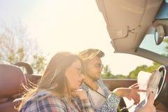 Junge liebevolle Paare, die ihr romantisches Abenteuer planen Frohe junge lächelnde Paare beim Reiten in ihr Kabriolett Lizenzfreie Stockfotografie