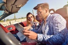 Junge liebevolle Paare, die ihr romantisches Abenteuer planen Frohe junge lächelnde Paare beim Reiten in ihr Kabriolett Stockbilder