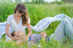 Junge liebevolle Paare, die im Gras umfassen lizenzfreie stockfotografie