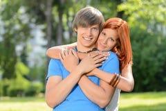 Junge liebevolle Paare, die im sonnigen Park umfassen Stockfotos
