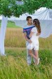 Junge liebevolle Paare, die unter einem Baum sich umfassen Stockfotografie