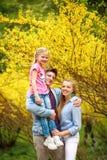 Junge liebevolle Paare von Eltern mit Kindertochter im Park auf Hintergrund des gelben blühenden Baums stockfotografie