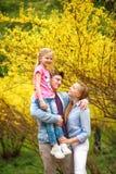Junge liebevolle Paare von Eltern mit Kindertochter im Park auf Hintergrund des gelben bl?henden Baums stockfoto