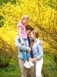Junge liebevolle Paare von Eltern mit Kindertochter im Park auf Hintergrund des gelben bl?henden Baums stockfotografie