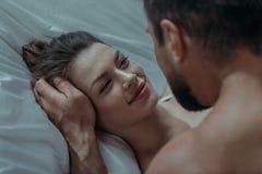 Junge liebevolle Paarumarmung im Bett Lizenzfreies Stockfoto