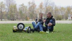 Junge Liebhaber, die auf dem Gras sitzen stock video