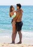 Junge Liebhaber, die auf sandigem Strand stehen Stockfotografie