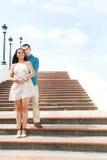 Junge Liebhaber, die auf Treppe umarmen Stockbild