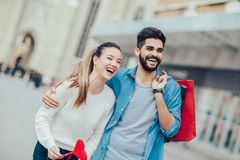 Junge Liebhaber, die ein großes rotes Herz und eine Einkaufstasche halten Stockbild