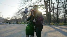 Junge Liebhaber im Rücklicht, Telefon auf Selbststock, Internet-Kommunikation, stilvoller Kerlmädchenweg im Park, stock video