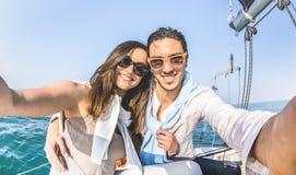 Junge Liebhaberpaare, die auf der ganzen Welt selfie auf Segelbootausflug - Liebeskonzept an der Jubiläumparteikreuzfahrt auf Lux stockfotografie