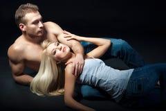Junge liegende und umarmende Paare lokalisierter Schuss Lizenzfreie Stockbilder
