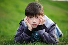 Junge liegt auf einem Gras Lizenzfreie Stockfotos