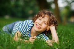 Junge liegt im grünen Gras, nachdem er den Kopf eine Hand er gesützt hatte Lizenzfreie Stockfotografie