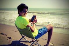 Junge liest ebook und kurze Hosen auf dem Strand mit Weinleseeffekt Lizenzfreies Stockfoto