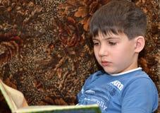 Junge liest ein Buch Stockbilder