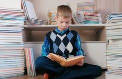 Junge liest ein Buch, das auf dem Boden unter den Büchern sitzt Stockbild