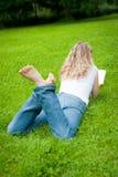 Junge lockige blonde Frau, die ein Buch in einem Park liest Stockfotografie