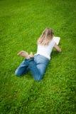 Junge lockige blonde Frau, die ein Buch in einem Park liest Lizenzfreie Stockfotografie