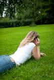 Junge lockige blonde Frau, die in einem Park telefoniert Stockfoto
