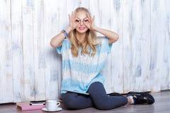 Junge lustige blonde Frau, die vor weißer hölzerner Wand sitzt Stockbilder