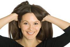 Junge lustige Frau mit den Händen in ihrem Haar Stockfotografie