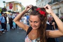 Junge lustige Frau mit Rosen im Haar steht auf dem Stadtplatz Stockfotos