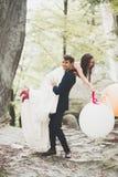 Junge lustige glückliche Hochzeitspaare draußen mit Ballons stockbild
