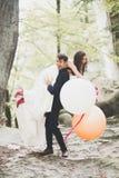 Junge lustige glückliche Hochzeitspaare draußen mit Ballons lizenzfreie stockfotos