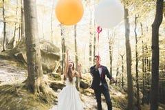 Junge lustige glückliche Hochzeitspaare draußen mit Ballons stockfoto