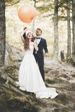 Junge lustige glückliche Hochzeitspaare draußen mit Ballons stockfotos