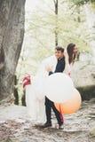 Junge lustige glückliche Hochzeitspaare draußen mit Ballons lizenzfreie stockfotografie