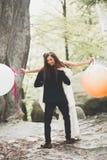Junge lustige gl?ckliche Hochzeitspaare drau?en mit Ballons lizenzfreies stockfoto