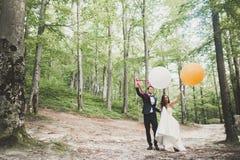 Junge lustige gl?ckliche Hochzeitspaare drau?en mit Ballons lizenzfreie stockfotografie