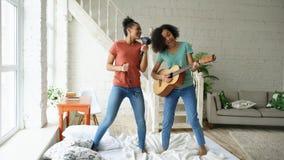 Junge lustige Mädchen der Mischrasse tanzen den Gesang mit hairdryer und das Spielen der Akustikgitarre auf einem Bett Schwestern Stockfotografie
