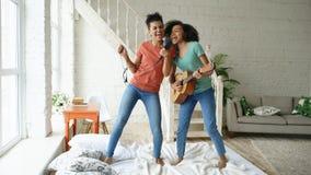 Junge lustige Mädchen der Mischrasse tanzen den Gesang mit hairdryer und das Spielen der Akustikgitarre auf einem Bett Schwestern Lizenzfreie Stockfotos
