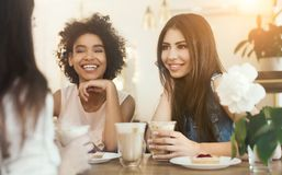 Junge lustige Mädchen, die im Café, in trinkendem Kaffee und in der Unterhaltung sitzen lizenzfreies stockbild