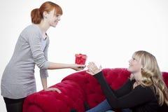 Junge Mädchen auf rotem Sofa haben einen anwesenden Kasten Lizenzfreies Stockbild