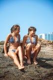 Junge Mädchen auf Steinen auf einem Strand stockfotos