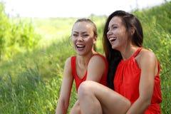 Junge Mädchen in den roten Kleidern lachen viel lizenzfreies stockfoto