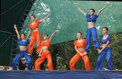 Junge Mädchen in der hellen Klage tanzen und zeigen akrobatische Bremsungen auf Sc Lizenzfreie Stockbilder