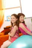 Junge Mädchen, die auf Übungskugel sitzen Stockbild